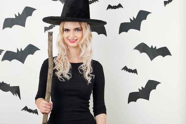 Jolie sorcière posant avec un balai