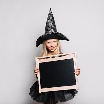 Jolie sorcière avec tableau noir