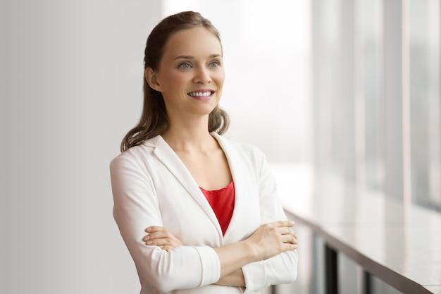 Jolie sourire d'affaires femme debout à la fenêtre