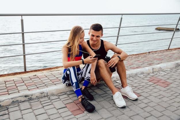 Jolie sportive et beau sportif regardant une vidéo drôle sur téléphone mobile
