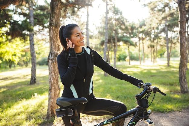 Jolie sportive avec un vélo dans le parc, écoutant de la musique avec des écouteurs sans fil