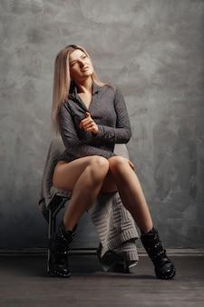 Jolie taille plus modèle assis sur une chaise près du mur abstrait grunge