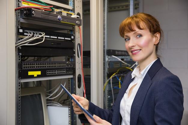 Jolie technicien à l'aide de tablet pc tout en fixant le serveur
