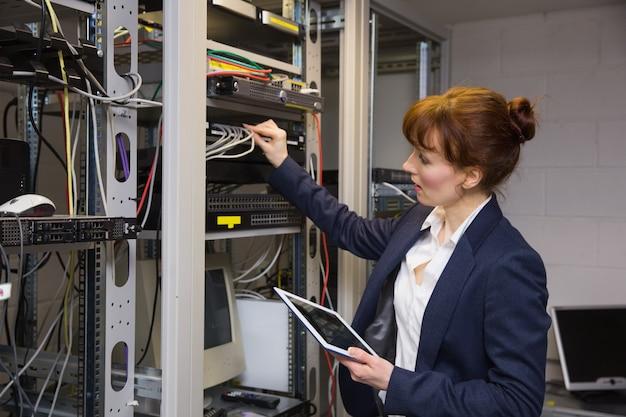 Jolie technicienne utilisant un tablet pc en train de réparer le serveur