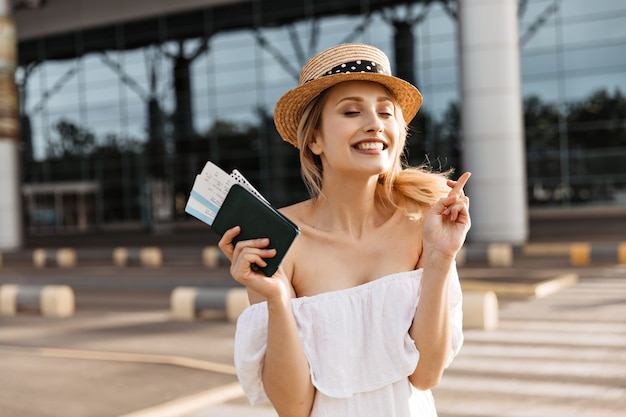 Une jolie touriste blonde détient un passeport et croise les doigts