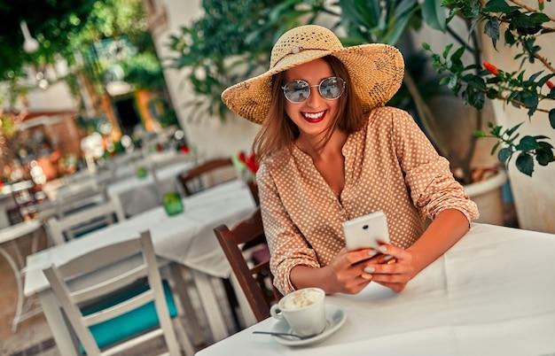 Une jolie touriste en lunettes de soleil, un chemisier et un chapeau de paille boit du café dans un café de la rue et utilise un smartphone. le concept de tourisme, voyage, loisirs.