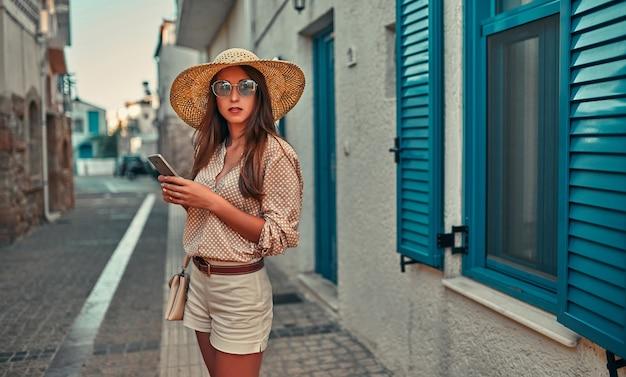 Une jolie touriste vêtue d'un chemisier, de lunettes de soleil et d'un chapeau de paille utilise un smartphone sur fond de maison aux volets bleus. le concept de tourisme, voyage, loisirs.