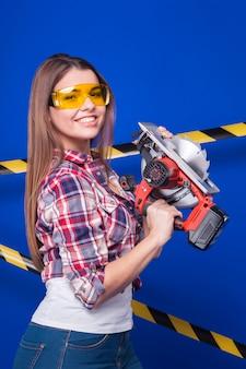 Jolie travailleuse sexy en chemise à carreaux, fabrique des lunettes et un pied en jean avec une scie circulaire
