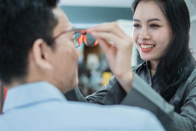 Une jolie vendeuse aide à mettre de nouvelles lunettes à un client masculin chez un opticien