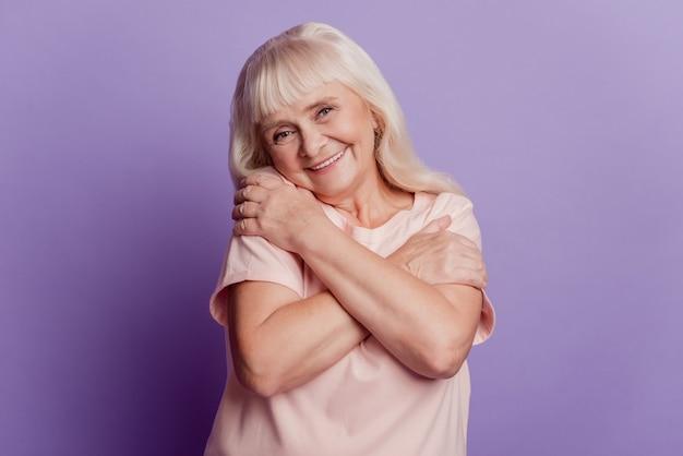 Jolie vieille dame s'embrassant isolée sur fond violet