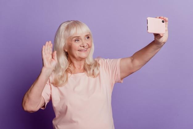 Jolie vieille femme aux cheveux gris faisant selfie isolé sur fond violet