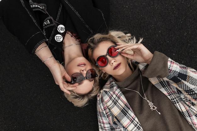 Jolies copines à la mode sexy avec de belles lèvres aux cheveux blonds dans des vêtements de jeunesse élégants dans des lunettes vintage se trouvent sur l'asphalte