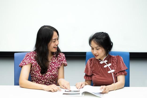 Jolies femmes asiatiques dans le style chinois cheongsam grande discussion joyeuse et entre collègues dans la salle de réunion au bureau avec bonheur et sourire dans le concept de succès, gagnant, réussi ou commercial