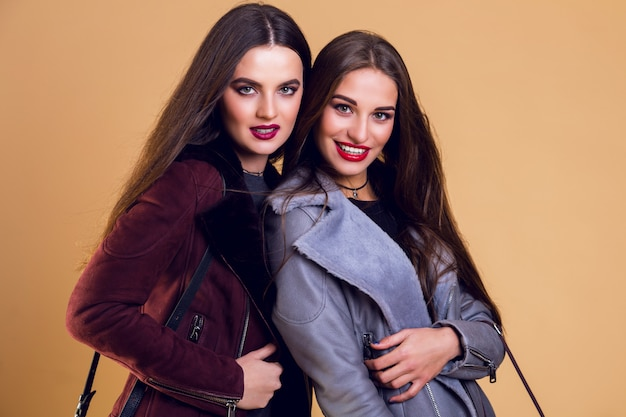 Jolies femmes glamour posant et portant des vestes d'hiver décontractées