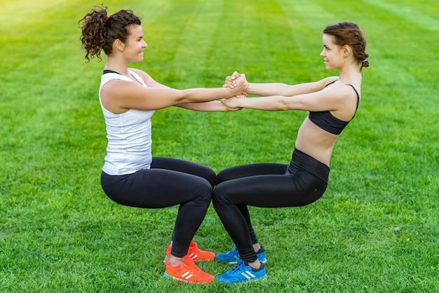 Jolies femmes heureuses portant des vêtements de sport faisant des exercices