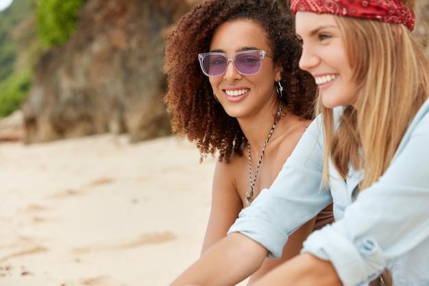 Les jolies femmes joyeuses s'amusent ensemble à la station balnéaire sur la plage, profitent de la convivialité et du temps chaud de l'été, regardent joyeusement la caméra, ont des sourires agréables. une femme africaine à la peau sombre se repose avec un ami