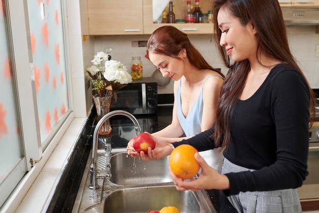 Jolies femmes lavant des fruits