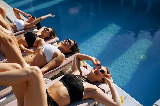 De jolies femmes à lunettes de soleil reposent sur des transats au bord de la piscine du complexe. de belles filles se détendent au bord de la piscine en journée ensoleillée, vacances d'été de copines séduisantes