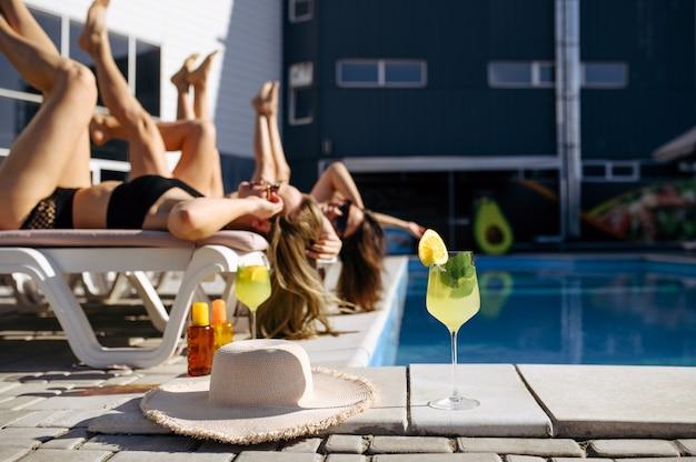 De jolies femmes en maillot de bain reposent sur des transats à la piscine du complexe. de belles filles se détendent au bord de la piscine en journée ensoleillée, vacances d'été de copines séduisantes