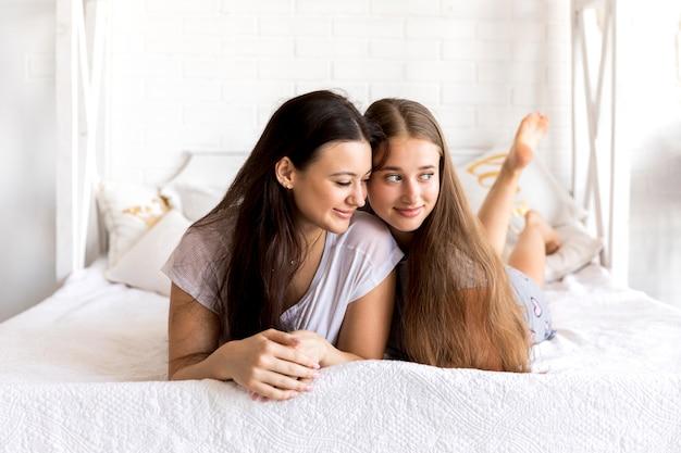 Jolies femmes qui cherchent loin sur le lit