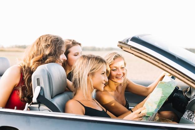 Jolies femmes regardant la carte en voiture