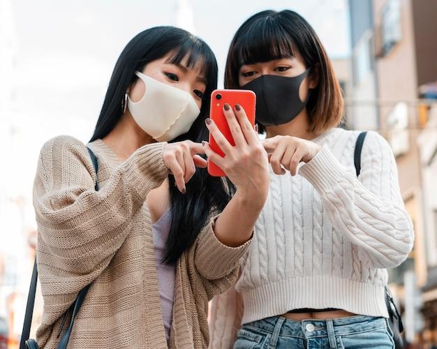 Jolies filles asiatiques portant des masques faciaux