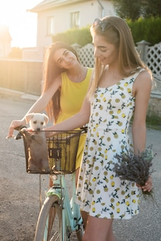Jolies filles avec un chien à vélo