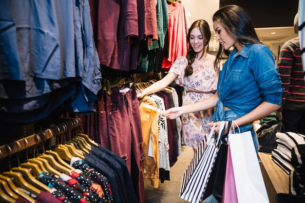 Les jolies filles choisissent des vêtements dans la boutique