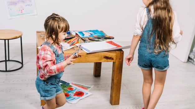 Jolies filles en cours d'exécution avec les doigts peints