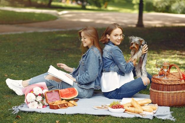Jolies filles dans un parc jouant avec petit chien