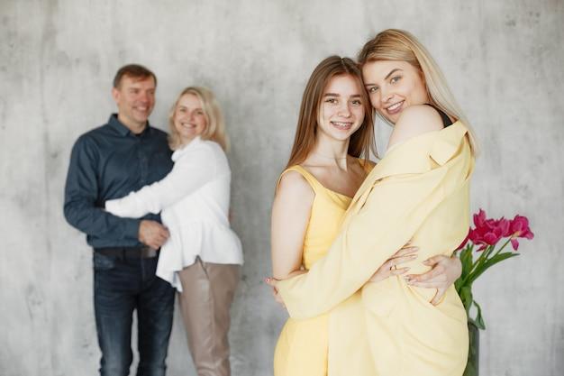 Jolies filles embrassant et parents étreignant floue derrière.