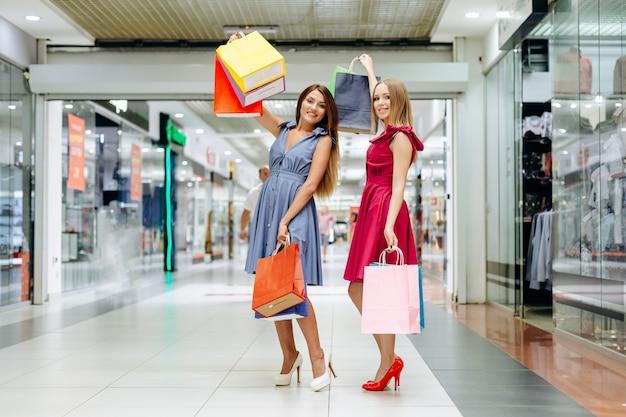 Jolies filles faire du shopping dans le centre commercial