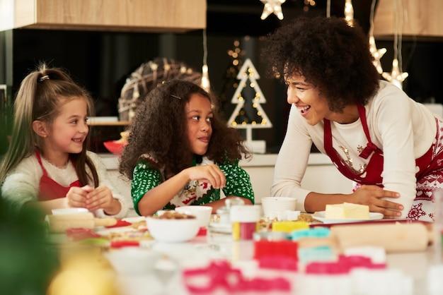 Jolies filles faisant des biscuits avec l'aide de leur maman