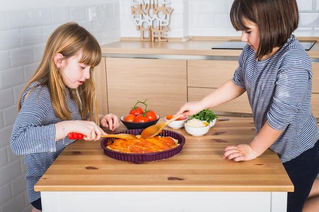 Jolies filles faisant une pizza maison ensemble