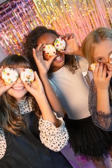 Jolies filles à la fête de fête tenant des petits gâteaux