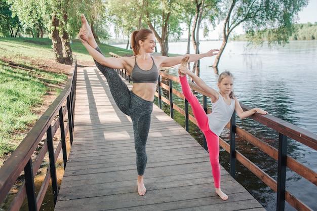 Les jolies filles font la même séance d'entraînement sur le pont