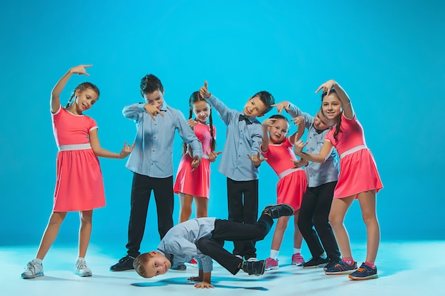 Jolies filles et garçons drôles dansant sur bleu
