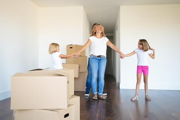 De jolies filles et leur père conduisent maman les yeux fermés dans leur nouvel appartement