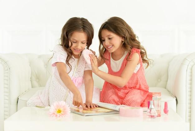Jolies filles avec magazine et cosmétiques à la maison