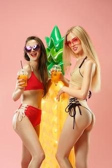 Jolies filles en maillot de bain posant au studio. portrait d'été adolescents caucasiens