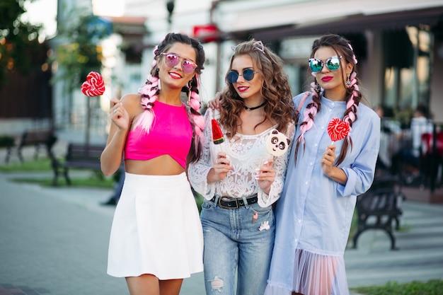 Jolies filles à la mode tenant coeur de bonbons sur bâton.