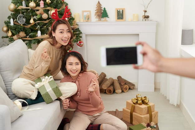 Jolies filles de noël montrant des cadeaux aux amis du téléphone portable.