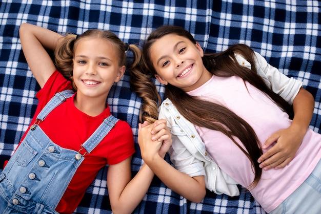 Jolies filles portant sur une couverture tout en se tenant la main