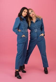 Jolies filles posant sur fond rose dans la tendance de la mode globale denim