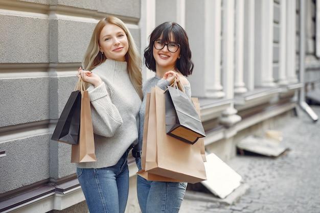 Jolies filles avec sac à provisions dans une ville