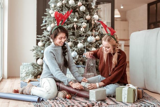 De jolies filles. sourire de filles aux cheveux longs portant des oreilles de cerf et emballant des cadeaux alors qu'il était assis près de l'arbre de noël