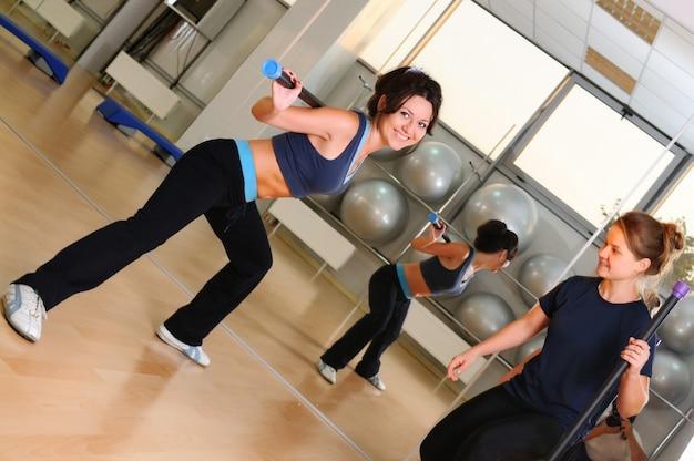 Jolies filles sportives en vêtements de sport faisant de l'exercice physique avec un bâton de gymnastique