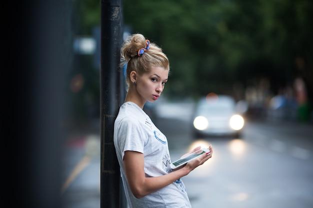 Jolies filles avec tablette sur un arrêt de bus