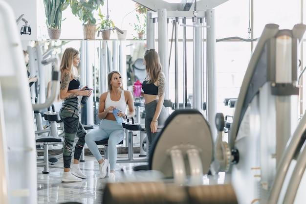 De jolies filles en tenue de sport au gymnase communiquent. vie sportive et ambiance fitness.