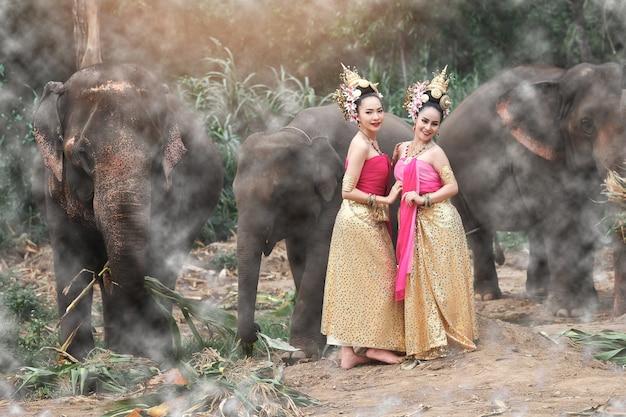 Jolies filles thaïlandaises en costumes traditionnels thaïlandais avec des éléphants
